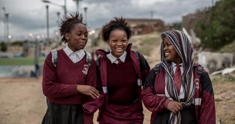 Three smiling girls walk to school together
