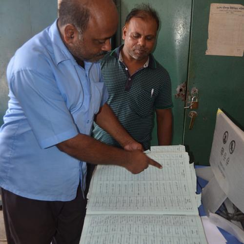 Man showing entries from a civil register to another man. Photo credit: Mia Harbitz
