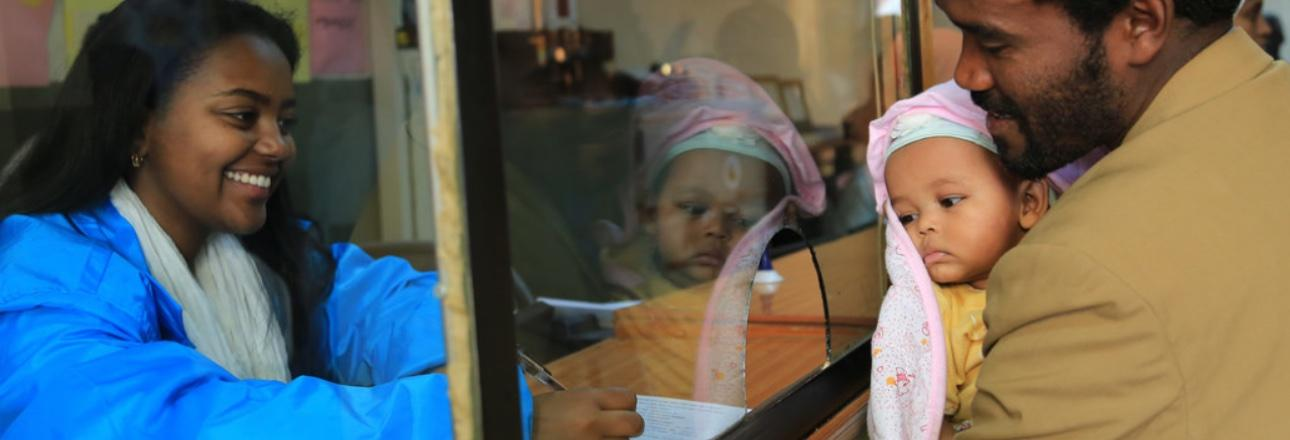 At the launch of a vital registration campaign in Ethiopia in 2016, a father registers the birth of his child. A female registrar records the details on an official form. Photo credit: UNICEF Ethiopia/Sewunet